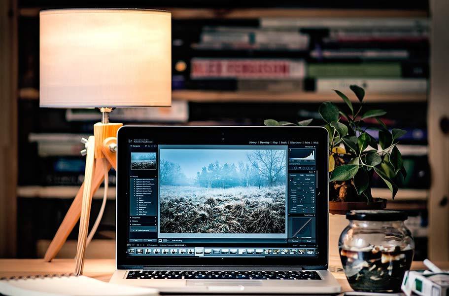 책상에 놓여진 맥북 컴퓨터 사진