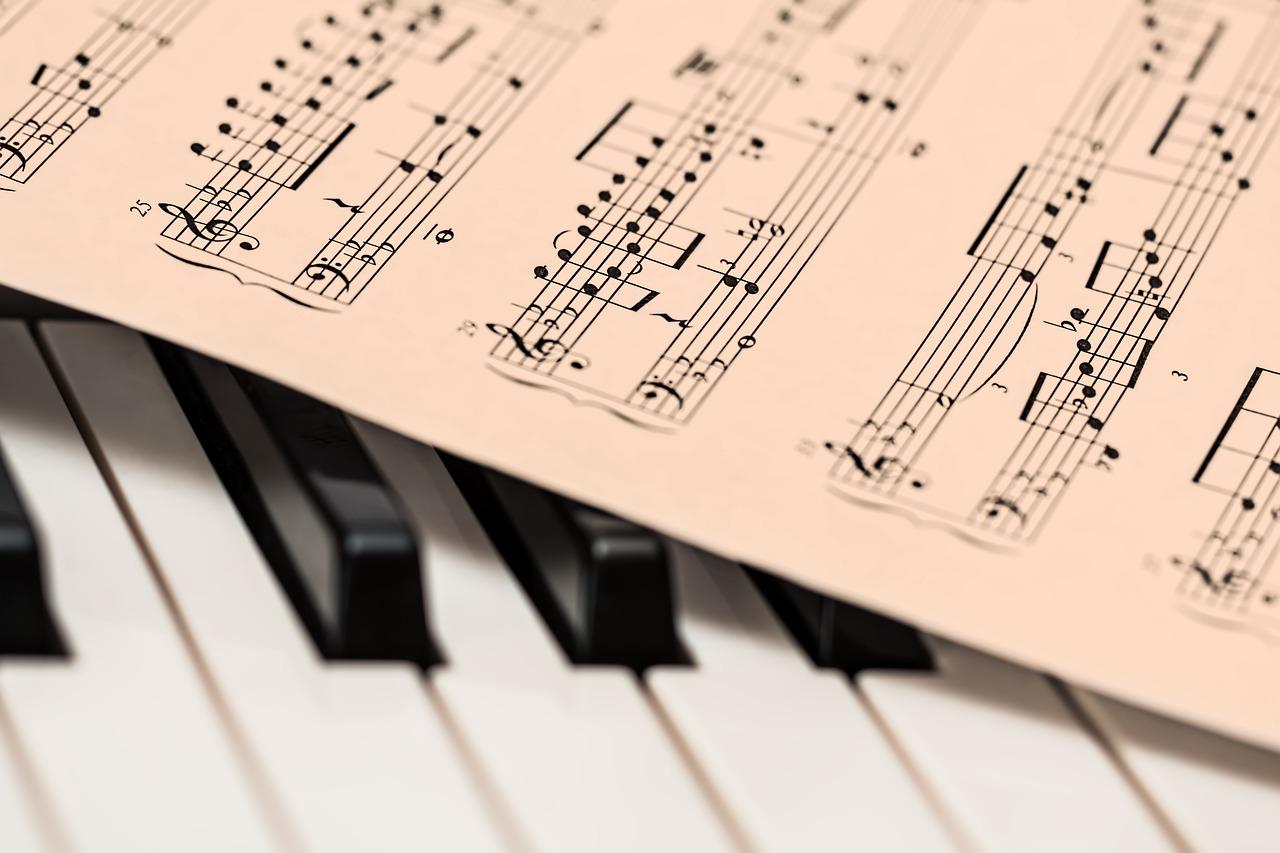 클래식 피아노 건반 위에 악보가 놓여있다